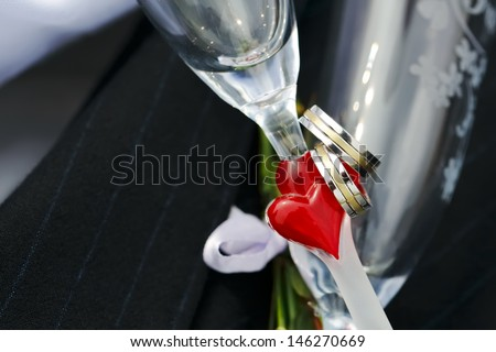 Wedding Rings and red heart on wedding glasses - stock photo