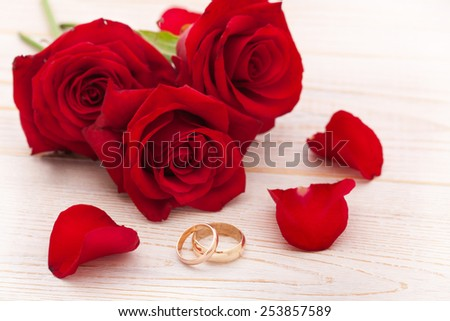 Wedding rings and wedding bouquet of red roses on wooden table, horizontally Selective focus, the background is blurred - stock photo