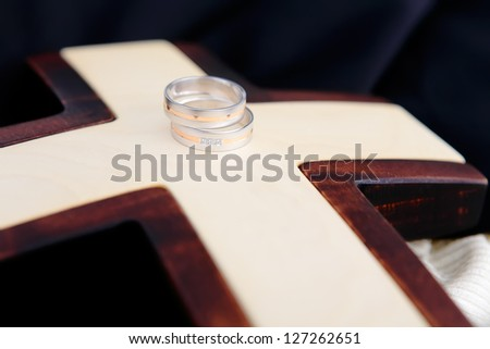 Wedding rings and wooden cross with wedding jacket in background, landscape photo orientation, focused to rings - stock photo