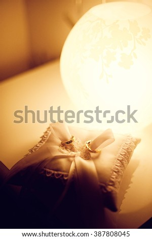 Wedding rings as wedding love symbol on the lace pillow in a warm light. Beautiful wedding background. - stock photo