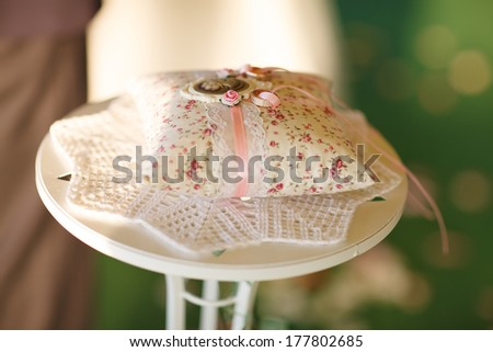 wedding rings at bridal ceremony, gold wedding rings on the pincushion, soft focus - stock photo