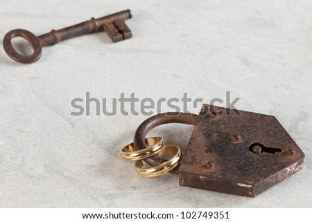 Wedding rings bound by a rusty lock