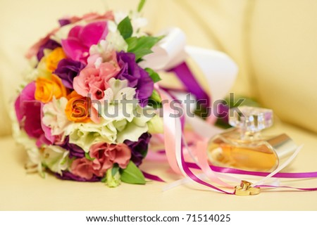 Wedding rings, bouquet and perfume, soft focus.