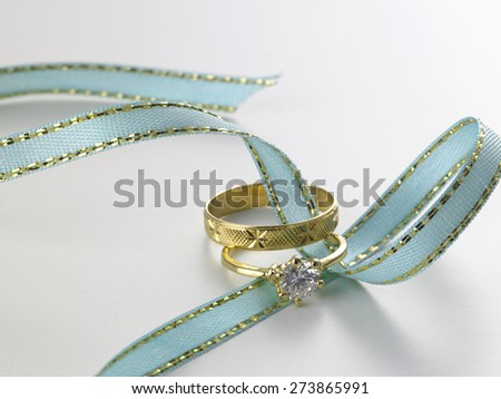 Wedding rings connected with green ribbon - stock photo