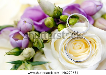 Wedding Rings detail with flowers, focused to the rings - stock photo