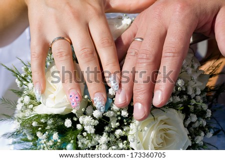 Wedding rings, hands and bouquet