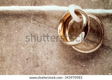 Wedding rings hanging on rope over a dirty canvas background - stock photo