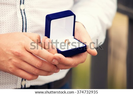 wedding rings in a blue box in a hand at the groom - stock photo