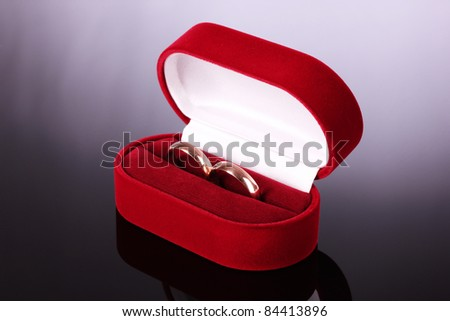 wedding rings in a box on a gray background