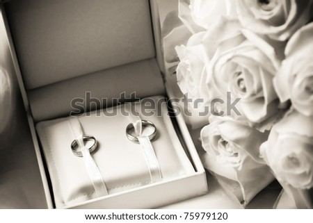 wedding rings in a box with bouquet with a shallow DOF - stock photo