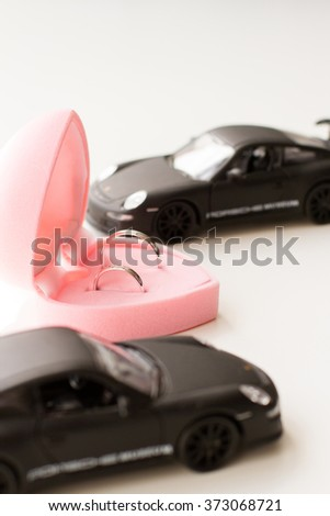 wedding rings in a pink box and two cars - stock photo