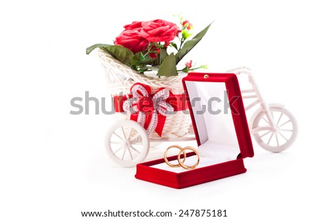 Wedding rings in a velvet box and a basket of flowers on a white background - stock photo