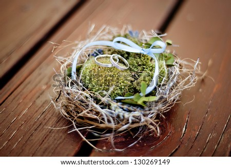Wedding rings in decorated nest - stock photo