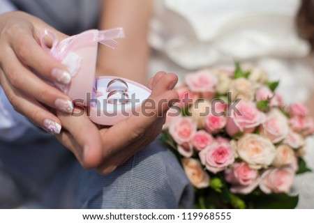 Wedding rings in hands of bride and groom. - stock photo