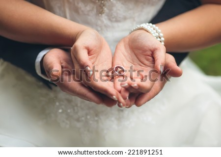 Wedding rings in hands of groom and bride - stock photo