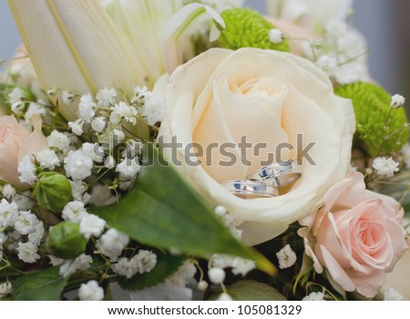 Wedding rings in rose bouquet - stock photo