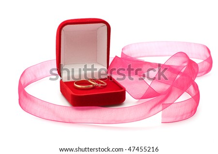 Wedding rings in the red box and a pink ribbon on a white background.