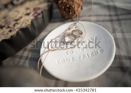 Wedding rings in white gold, white clay saucer with the word always have to be your friend - stock photo