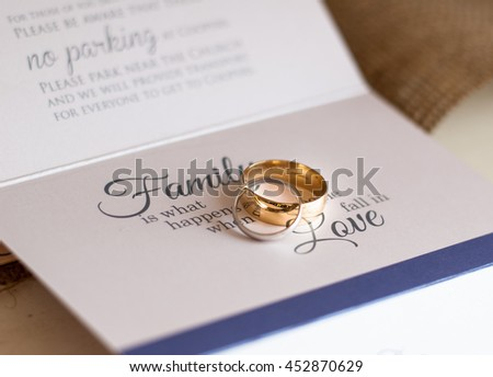 Wedding rings laying on a wedding invitation