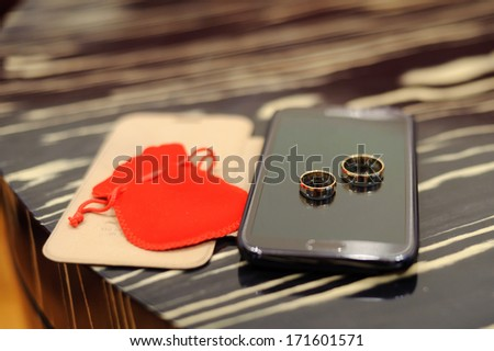 wedding rings laying on cell phone screen - stock photo