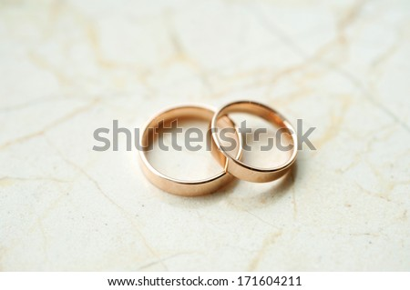 wedding rings laying on marble table - stock photo