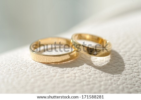wedding rings laying on white leather surface - stock photo