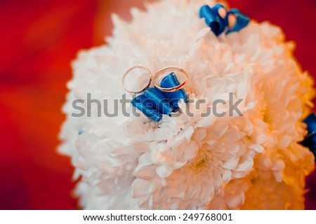 wedding rings lie on a bouquet of white with blue ribbons - stock photo