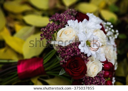 wedding rings lie on a wedding bouquet of red and peach, dairy roses and white flowers lying on yellow autumn leaves - stock photo