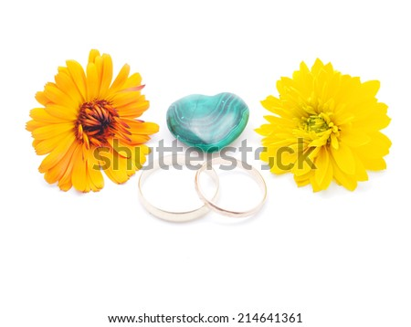 wedding rings, malachite heart and calendula on white background - stock photo