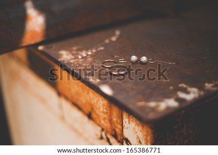 Wedding rings, necklaces bride on a dark background - stock photo