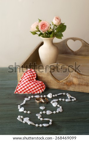 wedding rings on a background of flowers in a vase - stock photo