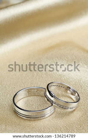 Wedding rings on a beige satin