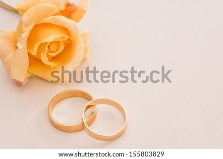 Wedding rings on a cream background with a yellow rose with space to add copy - stock photo