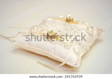 wedding rings on a cushion. - stock photo