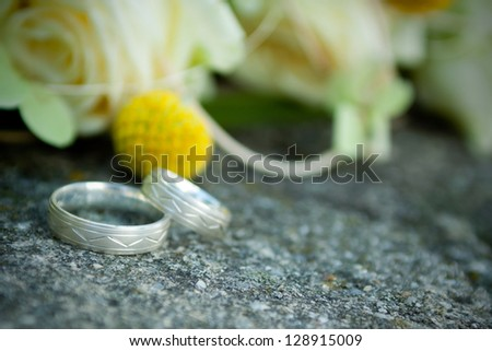 Wedding rings on a petal of a rose - stock photo
