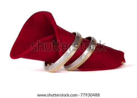 Wedding rings on a red petal of a rose - stock photo