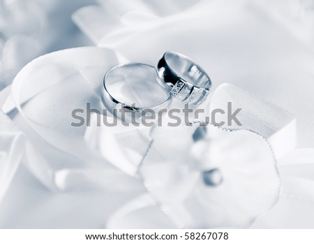 Wedding rings on a satiny fabric with bow