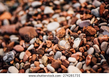 Wedding rings on beach. Wedding rings on  pebble - stock photo