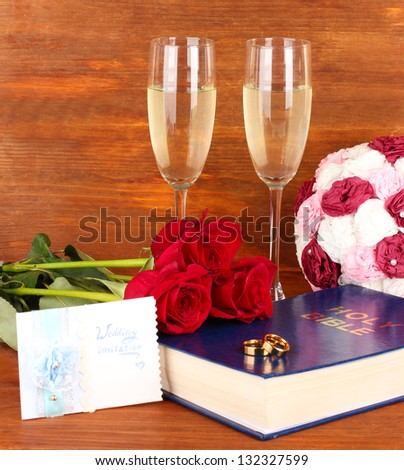 Wedding rings on bible with roses and glasses of champagne on wooden background
