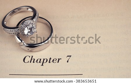 wedding rings  on book - stock photo