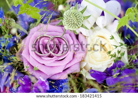 Wedding rings on bridal bouquet - stock photo
