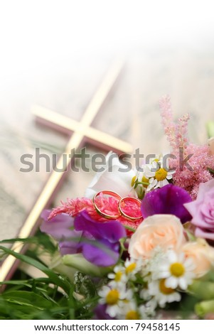 Wedding rings on bunch of flowers closeup with cross in background focused to th rings - stock photo