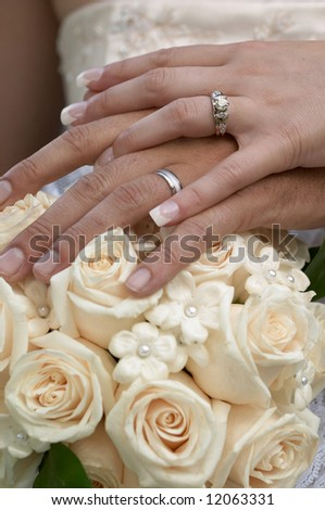 Wedding rings on hands of bride and groom, focus on rings - stock photo