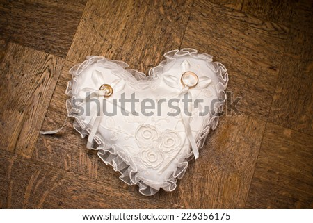 Wedding rings on heart shape pillow. - stock photo