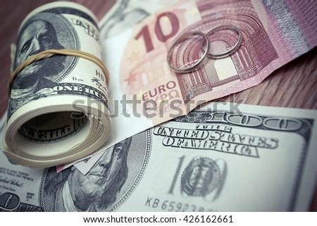 Wedding rings on money background - stock photo