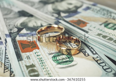 Wedding rings on money background, close up