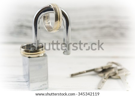 Wedding rings on opened shiny padlock and keys on vintage white background. Concept for marriage problems