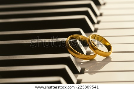 Wedding rings on piano - stock photo