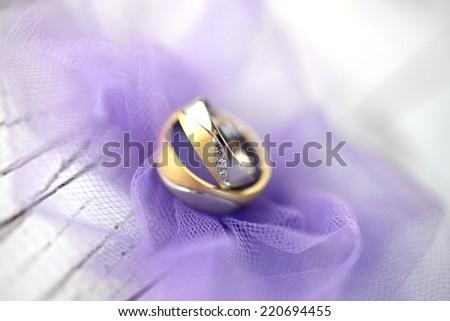 Wedding rings on purple tulle closeup - stock photo