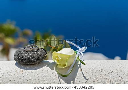 Wedding rings on stones and rose, on sea background